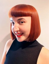 Copper red bob with a short fringe on a girl with red lipstick smiling at the klinik salon London