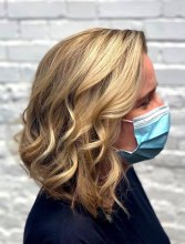 lady with a blonde graduated long bob tonged using GHD irons with a face mask and white brick wall as backdrop