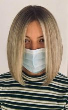 Lady in stripy top with a face mask having her hair blonde at the klinik salon London