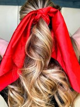 Blonde hair ponytail with a red bow at the klinik salon London