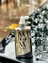 A silver colour hairrproduct from Color Wow stands on a black bench in the rain at the klinik salon promoting product of the week